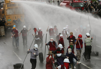 Protesters run away from water canon aimed by police as they march toward the headquarters of POSCO at a rally in Pohang