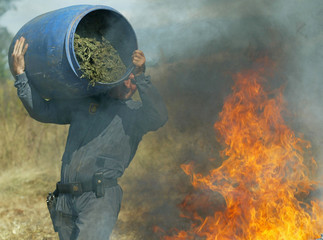 SOUTH AFRICAN POLICE CARRIES CONTAINER OF DRUGS TO BURN.