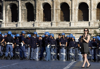 A tourist takes a picture in front of anti-riot police during a demonstration against the visit by U.S. President George W. Bush in Rome