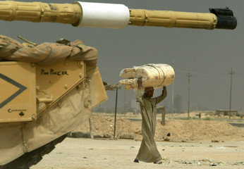 AN IRAQI MAN CARRIES MATRESS PASSED A TANK FROM THE BRITISH 7THARMOURED BRIGADE PATROL IN THE ...