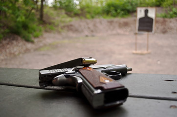 A pistol with a loaded magazine laying upon it with a blurred target behind it.