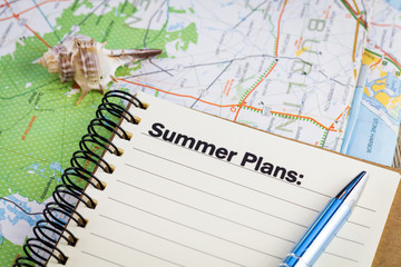 Summer plans list concept on notebook and map