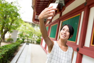Woman taking selfie by mobile phone in japanese temple