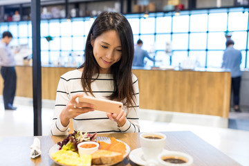 Woman taking photo on her dish in restaurant
