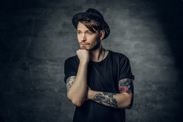 Thoughtful male with crossed tattooed arms, dressed in a black t shirt and tweed hat.