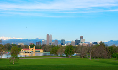 Downtown Denver skyline buildings, on a bright clear summer morning with lake and trees in foreground and snowcapped mountains in background.