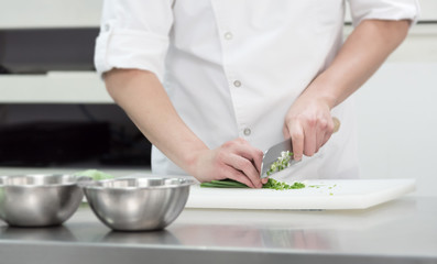 chef chopped fresh green onion on cutting board in kitchen