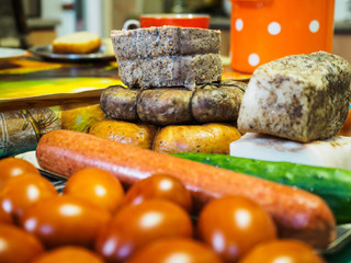 Easter background, brown chicken eggs, homemade sausages, boiled bacon with pepper, spices. Close-up view with soft focus and blur. Traditional Russian, Ukrainian homemade food for the Orthodox Easter