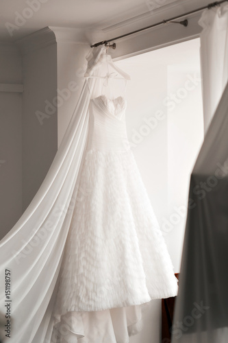 Beautiful wedding dress on hanger in room. the light from the window ...