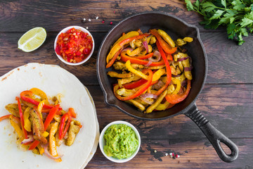 Chicken fajitas, fillet roasted with bell peppers and red onion in a black skillet, tortillas and traditional Mexican sauces salsa and guacamole. Wooden rustic table, top view.