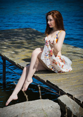 Gorgeous woman with porcelain skin in a lace embroidered pastel handmade swimwear . A girl rests and sits by the sun by the water on the bridge