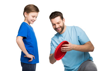 Father and son playing together with frisbee isolated on white