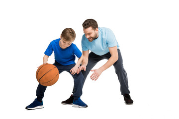 Father with son in casual clothes playing basketball isolated on white