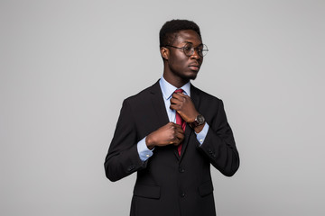 Afro amerocan business man in suit make his tie on grey background