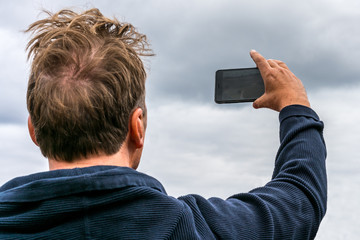 Man holding up mobile phone against cloudy sky to take pictures, upper body seen from behind.