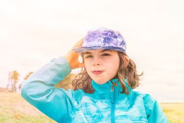 Sunny portrait of cute young girl in blue jacket and cap with wind in her hair, outdoors in open landscape.