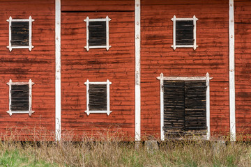Exterior of old abandoned decayed red barn with closed wooden window shutters.
