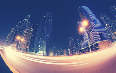 Fisheye lens long exposure distorted picture of Dubai downtown at night, color toning applied, United Arab Emirates.
