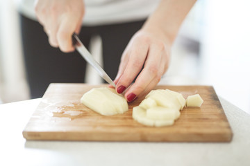 Cutting potatoes on close-up in real interior