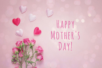 Mothers Day message with bouquet of roses and hearts on a pink background.