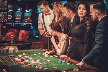 Upper class friends gambling in a casino Wall mural
