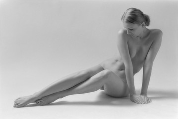 Beautiful blonde nude woman sitting on white background. Black & white film. Film grain. Copy space for text.