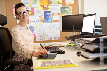 Portrait of smiling businesswoman working on digitizer at office