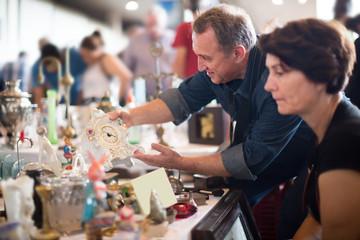 Glad tourists study the range of flea market