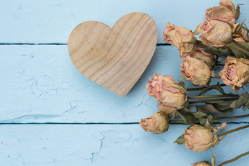 Natural wood carved heart with dried pink roses close up on blue painted wood planks as background