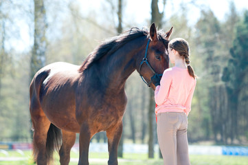 Young teenage girl standing with her favorite chestnut horse.