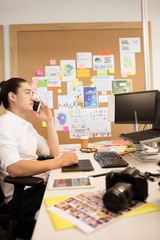 Designer talking on phone while working in creative office