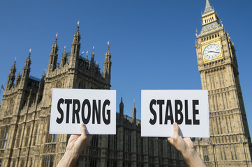 "Hands holding protest signs with the message ""Strong, Stable"" referring to the United Kingdom and its relationship with Europe during the Brexit transition in front of Westminster Palace in London"