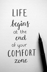 LIFE BEGINS AT THE END OF YOUR COMFORT ZONE written in brush calligraphy on notepad