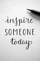 INSPIRE SOMEONE TODAY written in notepad on desk