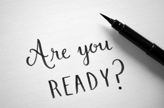 ARE YOU READY? written in notepad on desk with cup of coffee