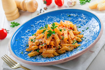 Traditional Italian meal made of penne pasta and arrabiata sauce with parsley on a white table. Delicious healthy Mediterranean food on a blue rustic plate.