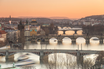 Orange sky at sunset on the historical bridges and buildings reflected on Vltava River, Prague, Czech Republic, Europe