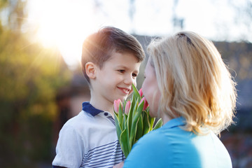 Little boy surprising mom with tulips at Mother's Day