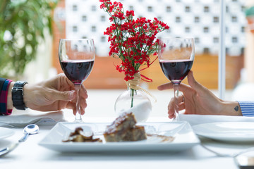 Couple holding wine glasses in the restaurant.