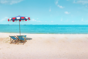 Two canvas beach bed and beach umbrella on the beach with nice sky and cloud at noon time.Holiday concept, relaxation