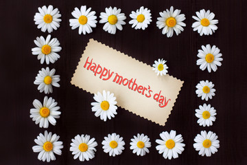 postcard happy mothers day/ Flat layout of chamomile flowers and greeting on a dark wooden surface top view