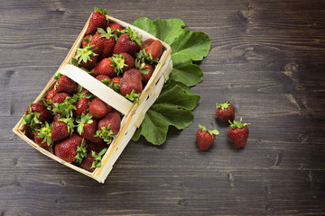 Small basket with juicy fresh strawberries on the wooden background, high angle view, summer concept