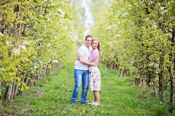 Couple standing in orchard looking towards camera, hugging each other