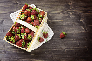 The basket to the top is filled with fresh strawberries on the wooden background, high angle view, summer concept