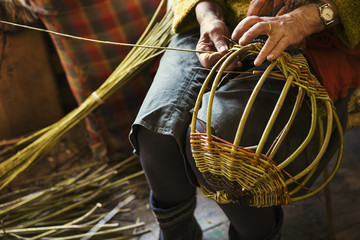 Close up of woman weaving a basket in weaver's workshop.