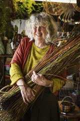 Smiling woman holding a willow bundle in a basket weaver's workshop.