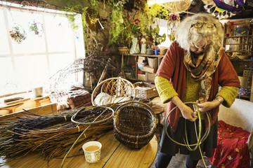 Woman weaving a basket in a weaver's workshop.