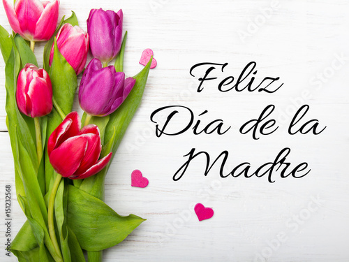 Mother's day card with Spanish words: Happy Mother's day, and  tulip bouquet on white wooden background