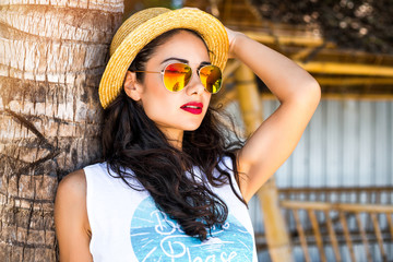 Close-up portrait of a young romantic dreaming cute hipster girl, a lady standing leaning on a palm tree, wearing a white top, wearing mirror sunglasses, a straw hat,  bright brunette, tropical island