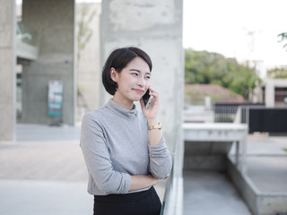 Asian business girl talking with smartphone in vintage color tone